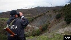 Një polic i Shqipërisë duke e vëzhguar kufirin me Greqinë