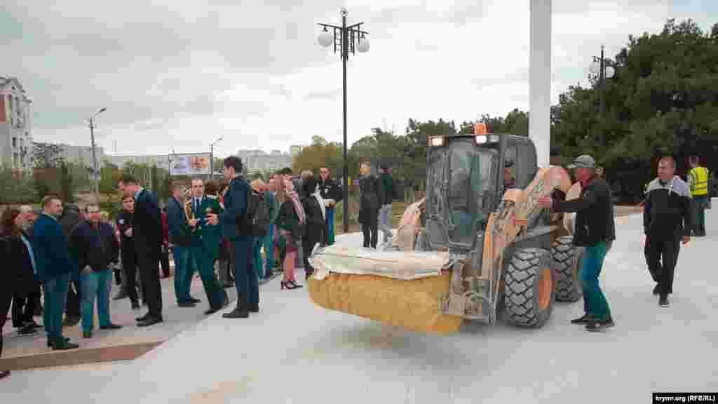 За несколько минут до прихода чиновников на подиум у входа в парк пригнали трактор для уборки от грязи и глины