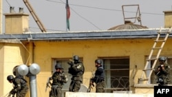 Afghan commandos try to enter the Justice Ministry building, which was attacked by militants in Kabul.