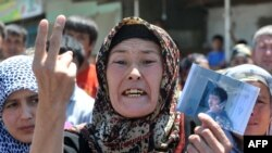 Женщина-узбечка плачет и показывает фото своего родственника, который был убит во время беспорядков. Ош, 20 июня 2010 года.