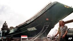 "Workers walk in front of the aircraft carrier ""Varyag"" at a dockyard in Mykolayiv in May 1997, before its transfer to Chinese hands."