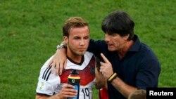 Германия құрамасының бапкері Йоахим Лев (оң жақта) финалда қосымша уақыт берілерге дейін шабуылшы Марио Гетцеге кеңес беріп тұр. Рио-де-Жанейро, 13 шілде 2014 жыл.