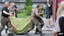 Пророссийские боевики несут тело погибшего во время нападения на пограничный командный центр в окрестностях Луганска, 2 июня 2014 года.