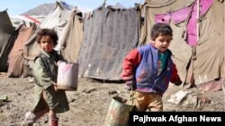 Internally displaced children carry water in Kabul. Many Afghans have no access to basic services like running water and electricity.