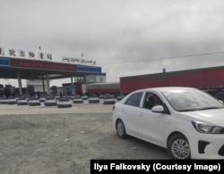 """Родственники ждут водителя машины у блокпоста при выезде из Кучара. Надпись на транспаранте: """"Горячо поздравляем с 70-летием со дня создания КНР!"""""""