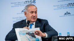 Israeli Prime Minister Benjamin Netanyahu shows a map of the Middle East during a panel discussion at the Munich Security Conference in Munich, February 18, 2018