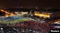 Бухарестте түндө чогулган демонстранттар Румыниянын үч түстүү желегинин түспөлүн чагылдырып турушту. 12-февраль, 2017-жыл.