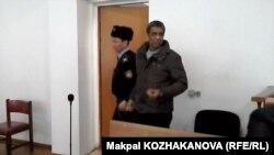 Қазақстанға «заңсыз миграция ұйымдастырды» деген айып тағылған Пәкістан азаматы Сарфараз Хуссаинді сот залынан полиция қызметкері әкетіп барады. Алматы, 23 қаңтар 2015 жыл.