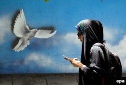 İranlı qadın Tehranın küçəsi ilə addımlayır.