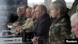 Президент России Владимир Путин и сын президента Беларуси Александра Лукашенко наблюдают за завершающим этапом совместных военных учений «Запад-2013». Беларусь, Гродно, 26 сентября 2013 года