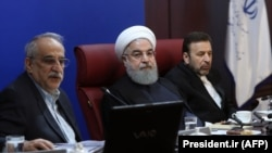 Iranian President Hassan Rohani (C) sits next to Minister of Economy during a meeting with members of the ministry, in Tehran, January 8, 2018