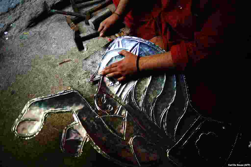 A metal worker hammers texture into a horse decoration destined for a truck in Rawalpindi.