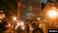 A street performer dressed as a bear is seen at a Christmas and New Year market, with the Kremlin's Spasskaya Tower seen in the background, at the Red Square in Moscow.