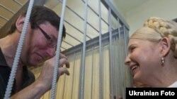 На фото 5 липня 2011 року Юрій Луценко був за ґратами, а Юлія Тимошенко на волі
