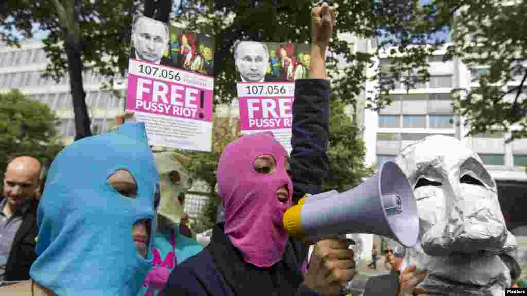 People wear caricature masks of Russian President Vladimir Putin and trademark Pussy Riot balaclavas during a support rally for the detained members outside the Russian Embassy in Berlin on August 17.