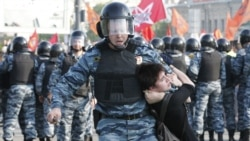 Russian riot police detain a female protester during an opposition protest in Moscow in May 2012.
