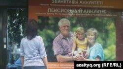 Сақтандыру компаниясының жарнамасын қарап тұрған әйел. Алматы, 12 мамыр 2013 жыл.