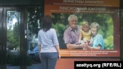 Женщина у офиса одной из компаний по страхованию жизни. Алматы, 12 мая 2013 года.