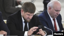 Chechen leader Ramzan Kadyrov (left) seems very attached to his cell phone and is an active Instagram user. (file photo)