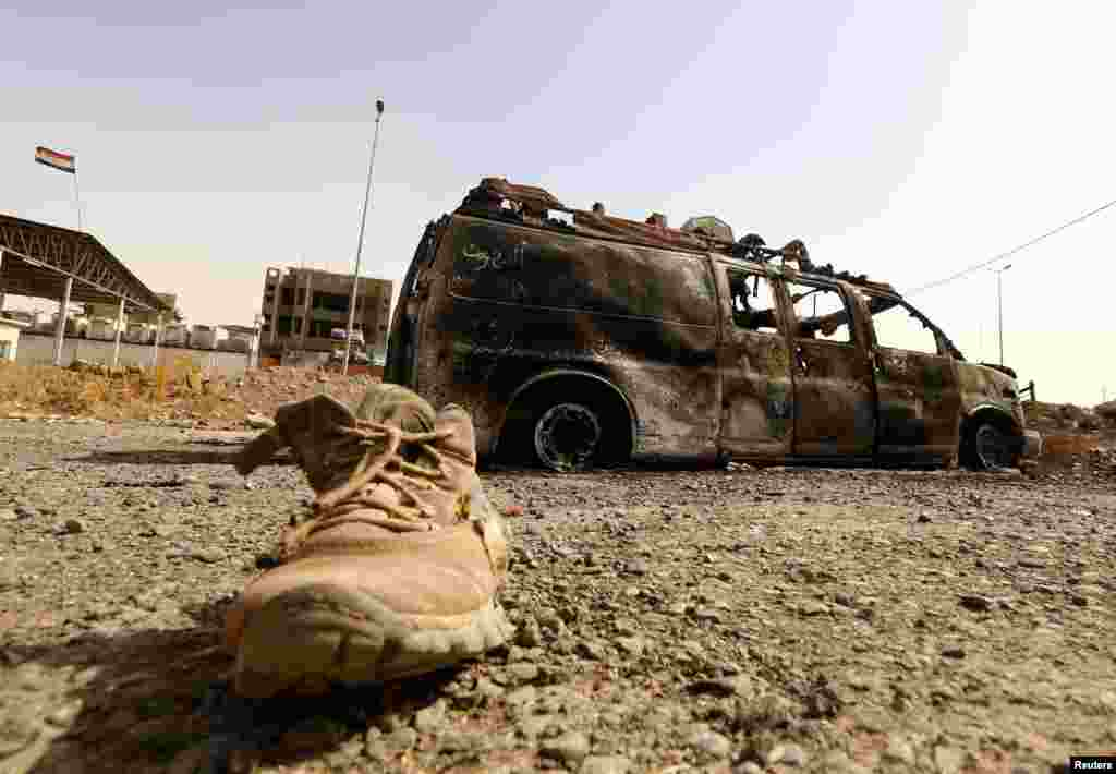 A burnt vehicle belonging to Iraqi security forces is pictured at a checkpoint in east Mosul, one day after radical Sunni Muslim insurgents seized control of the northern city, on June 11. (Reuters)