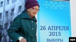 Пожилая женщина проходит мимо предвыборного билборда в Астане.