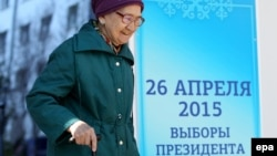 Пожилая женщина проходит мимо предвыборного баннера. Астана, 24 апреля 2015 года.