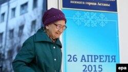 Кезектен тыс президент сайлауының мерзімі жазылған плакат жанынан өтіп бара жатқан егде әйел. Астана, 24 сәуір 2015 жыл.
