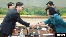 Делегації Південної (л) і Північної (п) Кореї на переговорах у демілітаризованому селищі Пханмунджом на кордоні між ними, 10 червня 2013 року, фото Міністерства об'єднання Південної Кореї