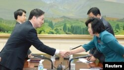 South Korea -- Head of South Korean delegation for an inter-Korean working-level talks, Chun Hae-sung (L) shakes hands with his North Korean counterpart Kim Song-hye, the southern side of the truce village of Panmunjom in the demilitarised zone, 09Jun2013