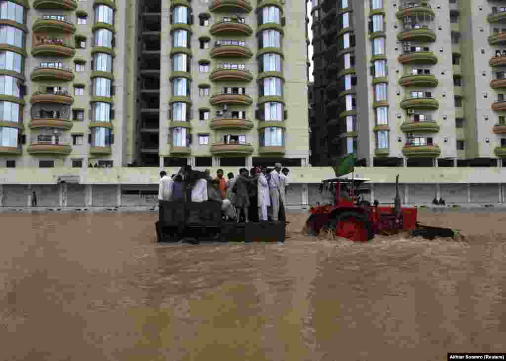 A tractor tows residents through floodwaters to a safe place on the outskirts of Karachi on August 4. Monsoon rains across Pakistan killed more than 100 people and affected hundreds of thousands.