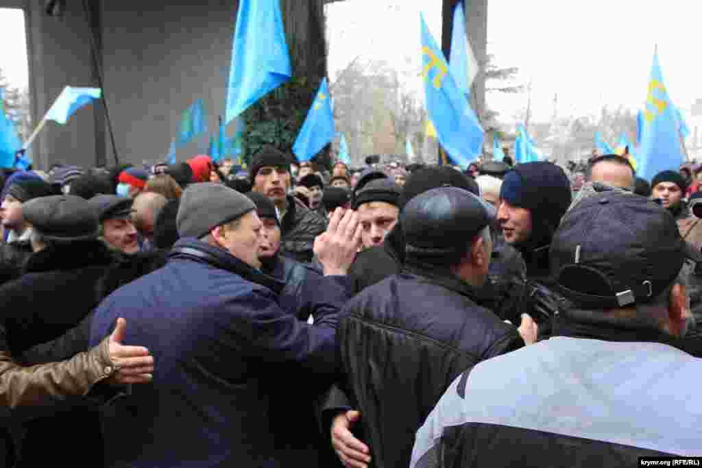 Ortada Qırımtatar Milliy Meclisi reisiniñ muavini Ahtem Çiygoz 2014 senesi fevral 26-da adamlarnı tuta
