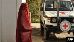 A woman waits at the ICRC office to leave for Bagram.