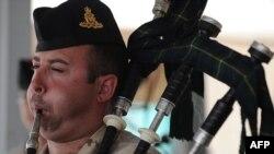 Канадски војник свири на гајда на почетокот на церемонијата на која канадските сили им ја предаваат контролата на воздухопловната база во Кандахар на американските сили.