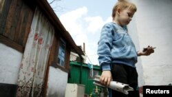 A boy holds the remains of a mortar shell which hit a residential building in a village outside the separatist-held city of Donetsk in the Donbas region, where fighting has reportedly intensified in recent days.