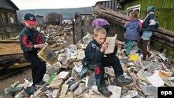 Дети на книгах и журналах из библиотеки, разрушенной наводнением. Ленск, 2001 год