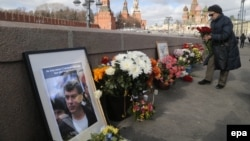 A woman lays flowers at the place where Boris Nemtsov was killed on February 26.