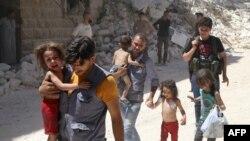 Сирийские мужчины несут детей среди обломков разрушенных зданий после воздушных ударов по повстанцам в районе Аль-Мешхед в Алеппо, 25 июля 2016 года