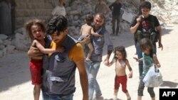 Сирійські чоловіки несуть дітей серед уламків зруйнованих будівель після повітряних ударів по Алеппо, 25 липня 2016 року
