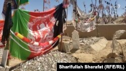 The Afghan flag and the Taliban banner top the graves of Faizullah's three brothers. Two of them were killed while working for the Afghan police while the other was a Taliban fighter. (video grab)