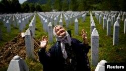 Жінка поруч з могилою свого родича на меморіальному кладовищі Поточарі. 10 липня 2015 року