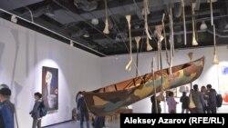 Лодка, подвешенная к потолку. Вокруг нее - палки с костями животных вместо лопастей. Это – инсталляция «Дождь».