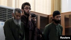Four Afghan men look on in court during their trial in connection with the killing of a 27-year-old Farkhunda, in Kabul on May 6.