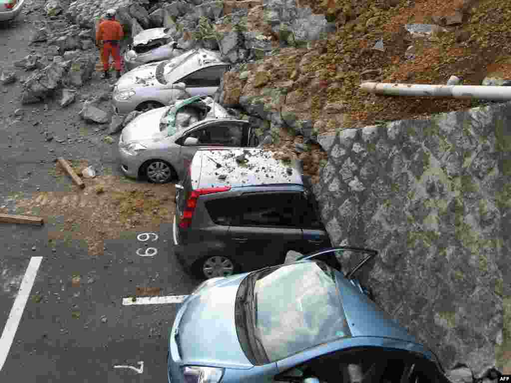 Vehicles are crushed by a collapsed wall at a car park in Mito city in Ibaraki prefecture after the earthquake. and tsunami.Photo by AFP