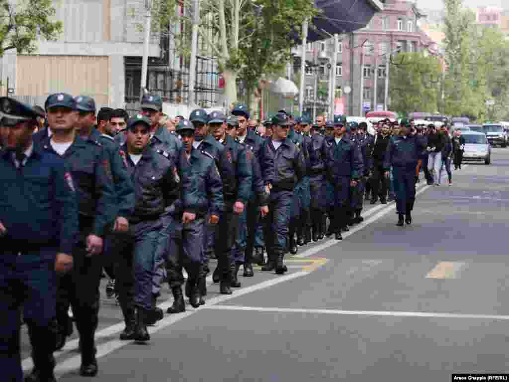 More than 100 police march alongside a protest led by Nikol Parshinian in Yerevan.