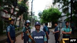 Bangladeshi policemen guard a check-point on a road block leading to the Holey Artisan Bakery, the scene of a fatal attack and siege, in Dhaka on July 3.