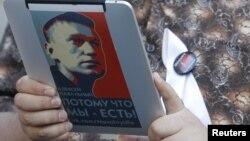 Алексей Навальныйдың суреті жапсырылған электрондық құрал ұстап тұрған оппозиция белсендісі. Мәскеу, 10 мамыр 2012 жыл. (Көрнекі сурет)