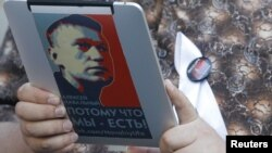 An opposition activist uses an electronic device with a portrait of prominent anticorruption blogger Aleksei Navalny during a protest in central Moscow last week.