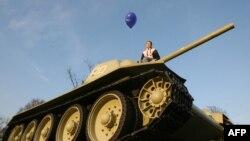 Девушка на танке, стоящем у Бранденбургских ворот в Берлине.