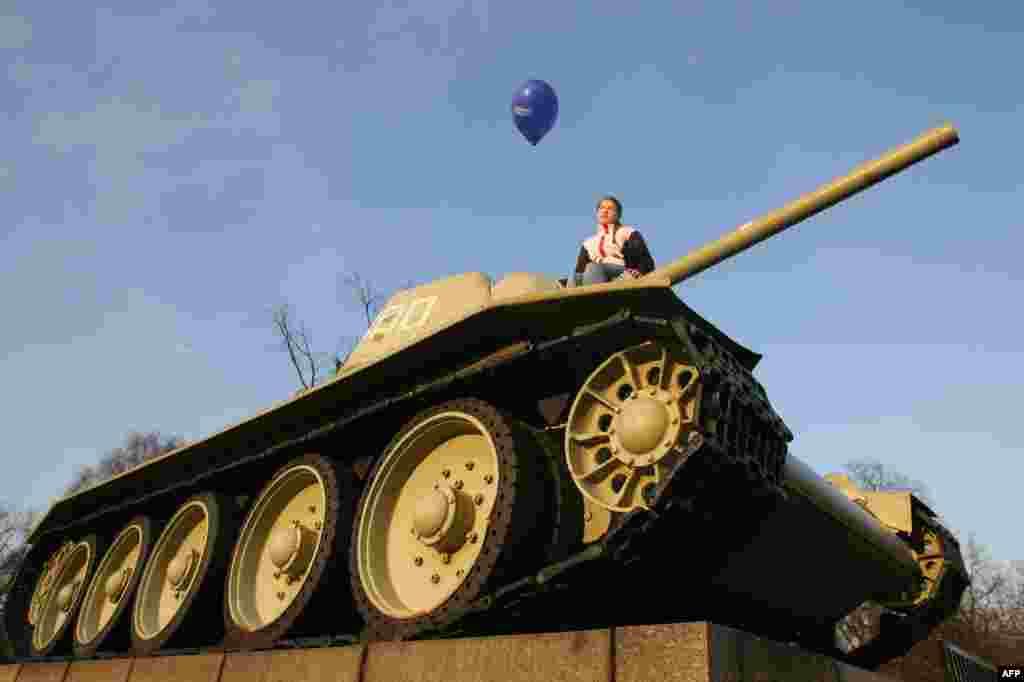 Germany -- A girl holds an EU balloon on a World War II era Soviet tank at the Soviet War memorial near Berlin's Brandenburg Gate, March 24, 2007