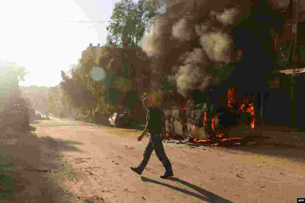 A Syrian man walks past a bus set ablaze following a reported air strike in the rebel-held Salaheddin district of Aleppo. (AFP/Ameer Alhalbi)